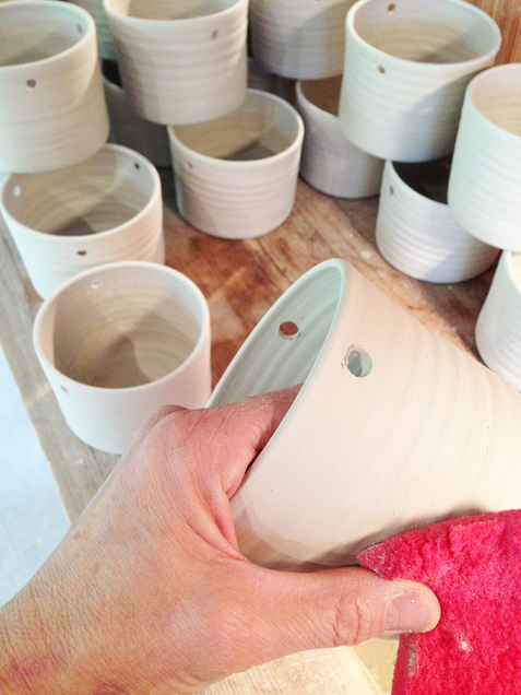 Hanging pots are being polished.